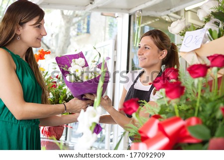 Portrait of an attractive and smiling woman customer client buying a bouquet of white fresh flowers from a fresh flower market stall store and young shop attendant. Outdoors business shopping.