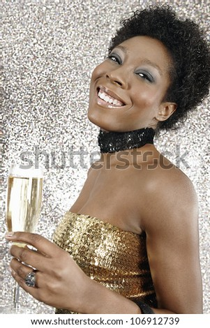 Portrait of an attractive black girl holding a glass of champagne on a silver glitter background, smiling.
