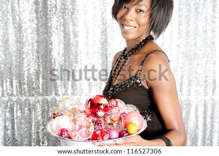 Portrait of an attractive black woman holding a dish full of christmas bar balls against a silver sequins background.