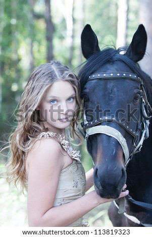 Portrait of an attractive blond girl with her horse.