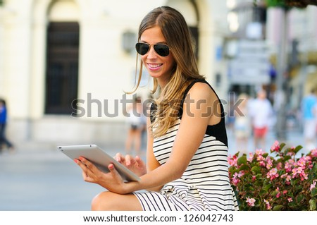 Portrait of an attractive blonde woman with tablet computer in urban background