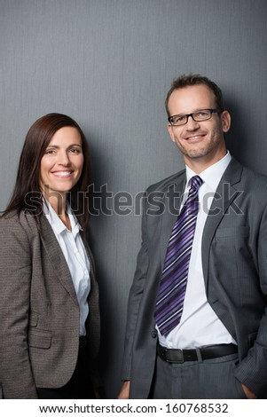Portrait of an attractive business couple leaning against a gray wall
