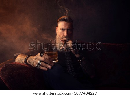 Portrait of an attractive business man with a cigar and a glass of whiskey in a dark room #1097404229