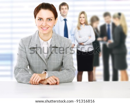 Portrait of an attractive business woman smiling with colleagues working in background