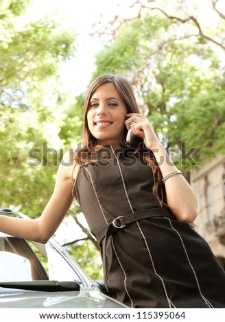 Portrait of an attractive businesswoman leaning on a car in a tree lined street, having a conversation with her cell phone.