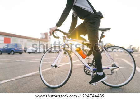 Portrait of an attractive cyclist in motion. Young rider in dark bike wears a bike on a street background and sunshine in the sunset. Transport and people.Cycling as a hobby #1224744439