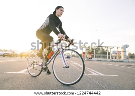 Portrait of an attractive cyclist in motion. Young rider in dark bike wears a bike on a street background and sunshine in the sunset. #1224744442