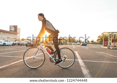 Portrait of an attractive cyclist in motion. Young rider in dark bike wears a bike on a street background and sunshine in the sunset. #1224744448