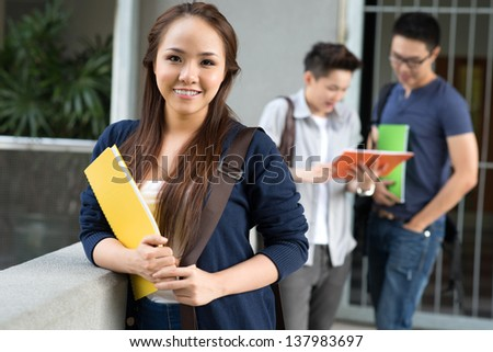 Portrait of an attractive female student on the foreground