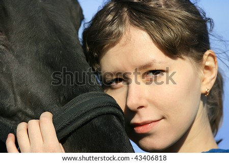 Portrait of an attractive girl, cuddling her black horse.