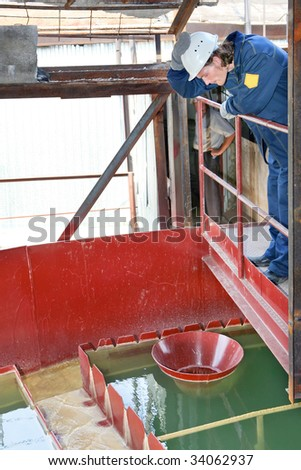 Portrait of an attractive industrial worker on the treatment plant background