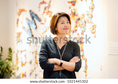 Portrait of an attractive Korean, Chinese or Taiwanese businesswoman in a professional black dress standing in an office with her arms crossed. She looks very smart, confident and happy.