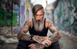 Portrait of an attractive man with a beard and tattoos in a street full of graffiti