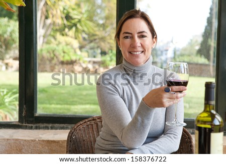 Portrait of an attractive mature woman sitting in a home interior with large glass windows and a green garden, relaxing drinking wine and smiling at the camera, indoors.