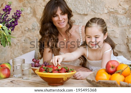 Portrait of an attractive mother and her young daughter eating fresh fruit in a holiday home outdoors, with the girl reaching to pick a strawberry. Healthy family lifestyle eating and living.