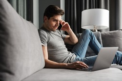 Portrait of an attractive serious young bearded man wearing casual clothes sitting on a couch at the living room, talking on mobile phone while using laptop computer