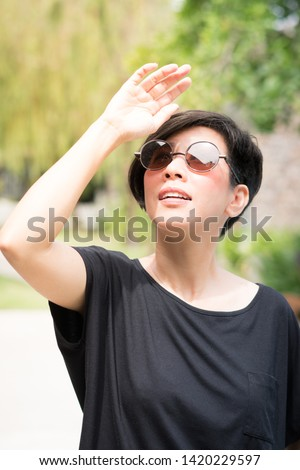 Portrait of an attractive short hair asian woman wearing 100% UV light protect sun glasses while she's outdoor. Risk of Eye Damage from UV Light, Protect skin and eyes from UV concept.