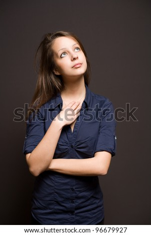 Portrait of an attractive slender young brunette woman pondering. - stock photo