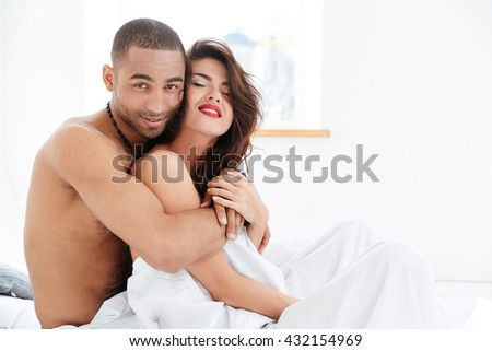 portrait of an attractive smiling sensual young couple caressing laying in bed together stock. Black Bedroom Furniture Sets. Home Design Ideas