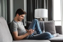 Portrait of an attractive smiling young bearded man wearing casual clothes sitting on a couch at the living room, using mobile phone
