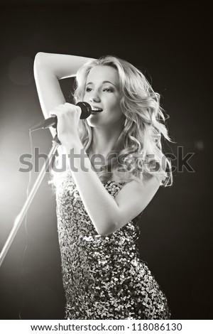 Portrait of an attractive teenager girl  singing with microphone. Black-white image