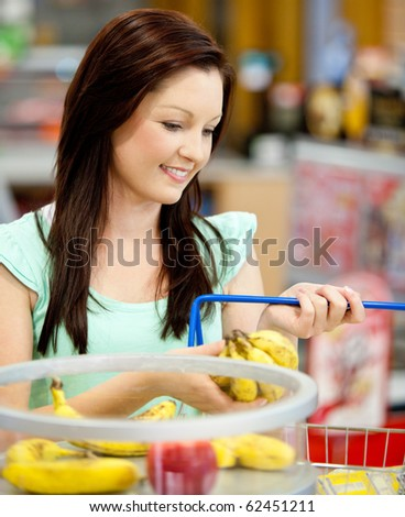 Portrait of an attractive woman buying bananas and apples in a grocery store