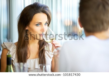 Portrait of an attractive woman drinking wine while on a date with her boyfriend