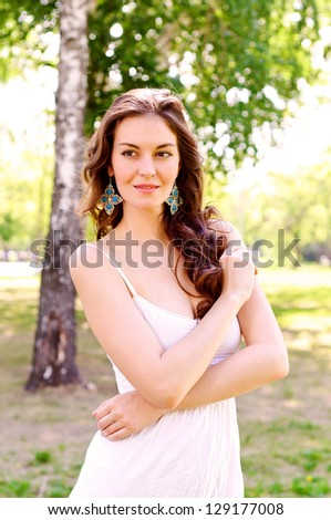 Portrait of an attractive woman in the park, crossed her arms