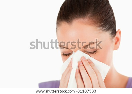 Portrait of an attractive woman sneezing while standing against a white background