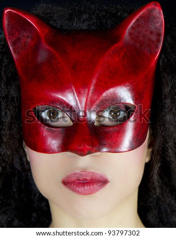 Portrait of an attractive woman wearing a red venetian mask. She is looking at camera. She is posing in front of a black background.