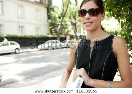 Portrait of an attractive young businesswoman holding a laptop computer under her arm and wearing shades while in a leafy street in the city with classic architecture. - stock photo