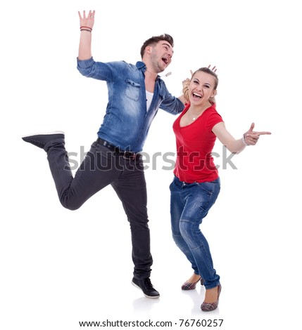 Portrait of an attractive young couple celebrating success with hands raised over white background