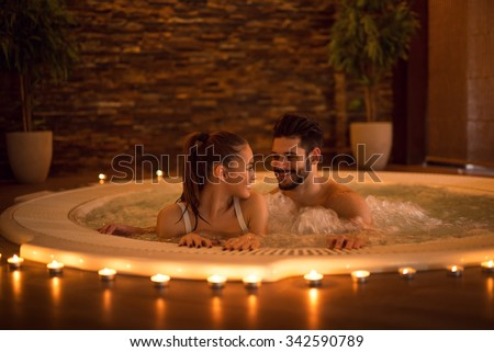 Portrait of an attractive young couple relaxing in a jacuzzi. High ISO image, ambiental light only.