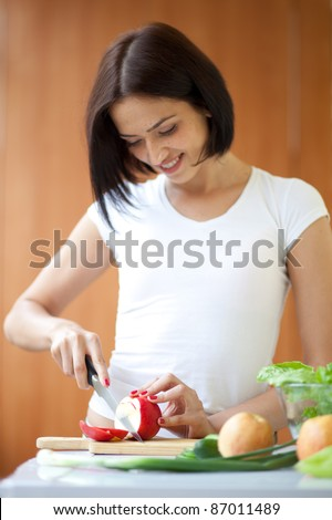 Portrait of an attractive young female cooking in the kitchen at home. Focus at the apple.