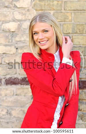 Portrait of an attractive young girl in red smiling against wall background