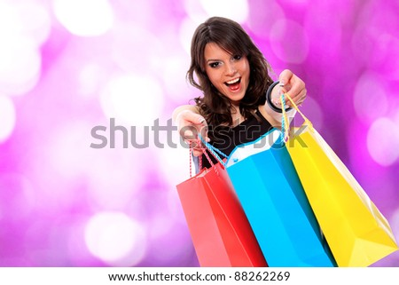 Portrait of an  attractive young girl with shopping bags in front of nice pink bokeh background