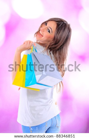 Portrait of an  attractive young girl with shopping bags in front of the shop - stock photo