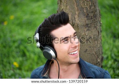 Portrait of an attractive young man relaxing outdoors and listening to music on headphones