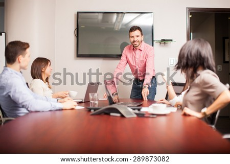 Portrait of an attractive young man talking to the rest of his team and smiling