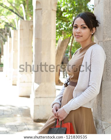 Portrait of an attractive young woman holding her shopping bags while leaning on a stone column in a romantic garden, outdoors.