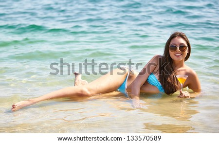 Portrait of an attractive young woman lying in water with a glass of cocktail