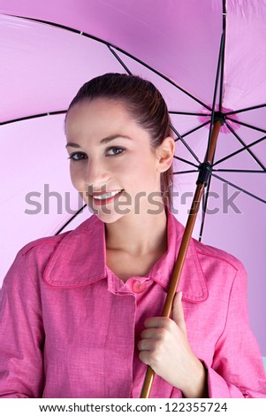 Portrait of an attractive young woman under a bright pink umbrella wearing a pink rain coat and smiling at the camera.
