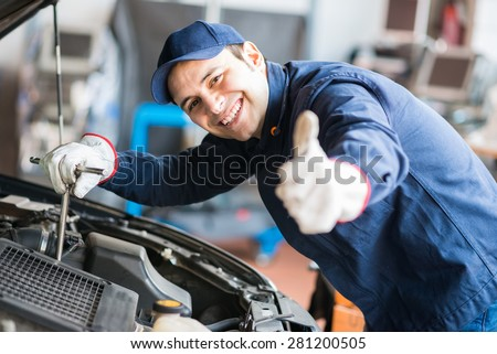 Portrait of an auto mechanic at work on a car in his garage #281200505