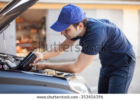 Portrait of an auto mechanic putting oil in a car engine #353456396