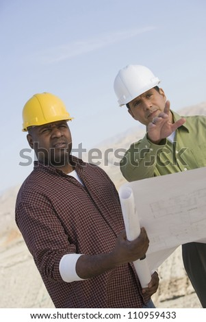 Portrait of an builder and supervisor holding blueprint at construction site