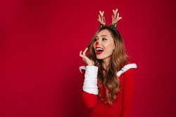 Portrait of an cheerful happy girl wearing christmas deer costume while standing and looking away at copy space isolated over red background