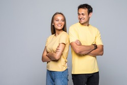 Portrait of an couple standing back to back over gray wall