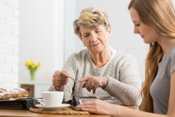 Portrait of an elderly lady having coffee with her granddaughter and showing an old photograph to her