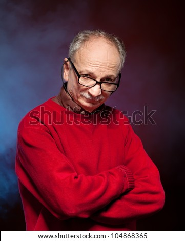 Portrait of an elderly man wearing glasses and a red sweater