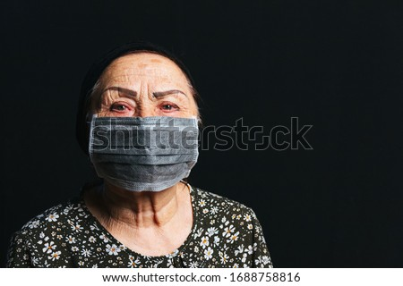 Portrait of an elderly woman in medical mask on a black background.   Old people in risk zone because of virus epidemy, COVID-2019 pandemic